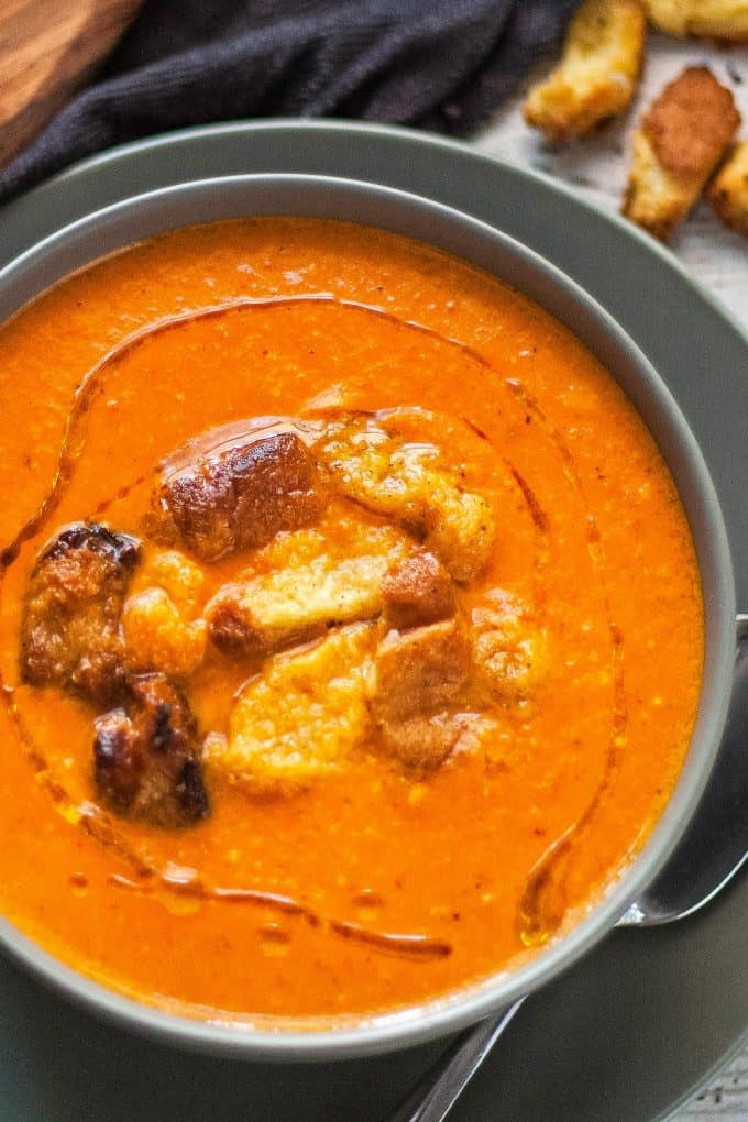 bowl of brie and roasted red pepper soup with brioche croutons