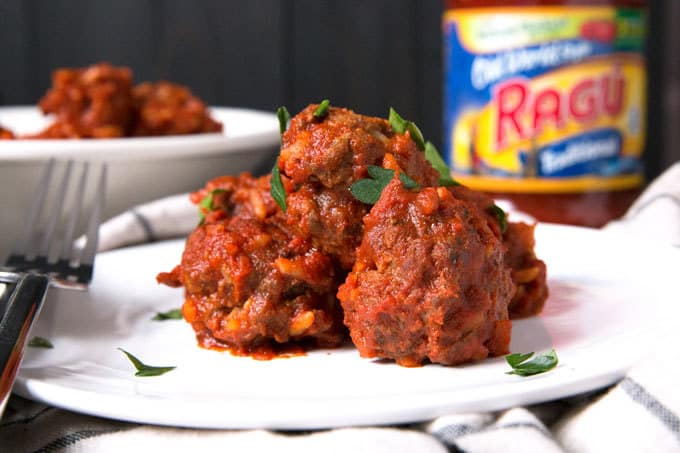 meatballs on a plate with bowl of meatballs in background