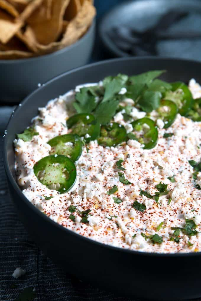 corn dip topped with jalapenos and cilantro
