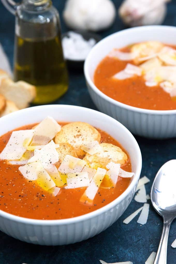 two bowls of roasted garlic tomato soup with croutons and parmesan cheese