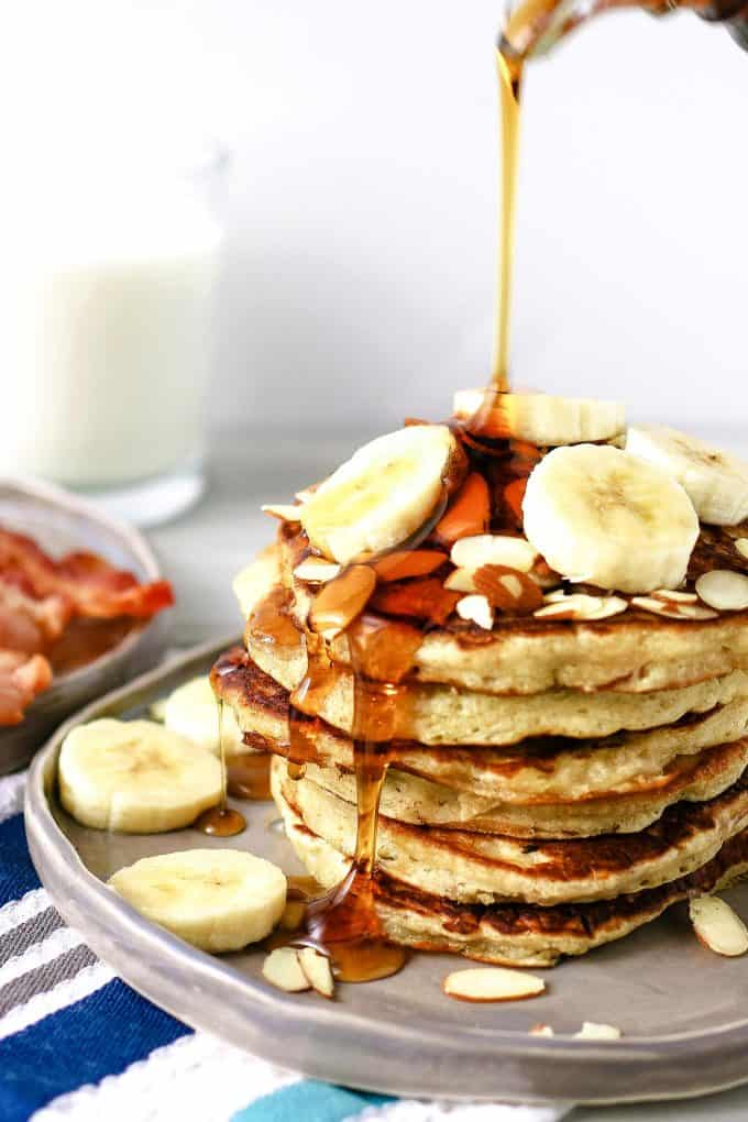 plate of almond banana pancakes with syrup being poured over fresh banana