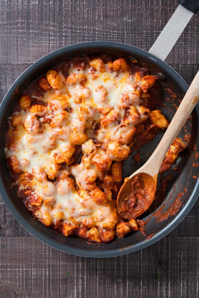 one pan cheesy gnocchi in a pan with a wooden spoon
