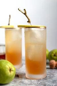 two sparkling bourbon pear cocktails with pear garnishes