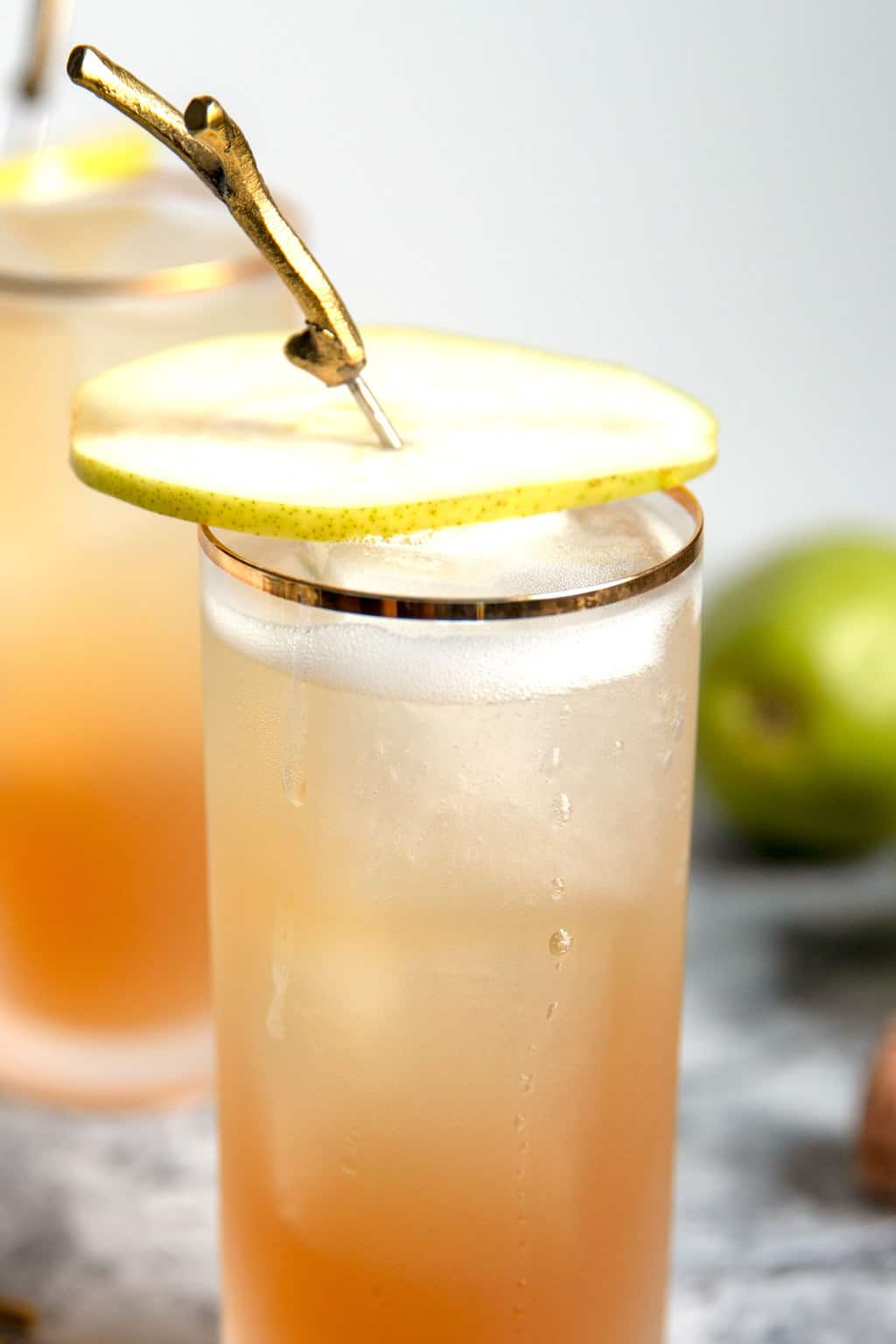 one sparkling bourbon pear cocktail with a pear garnish