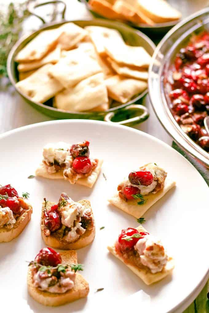 crackers in a bowl and topped with roasted cranberries and baked goat cheese