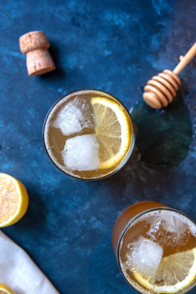 two sparkling honey rye whiskey cocktails and a wine cork