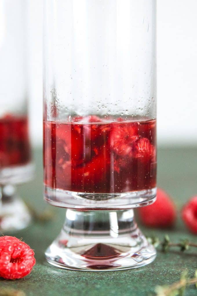smashed raspberries in a glass with Chambord