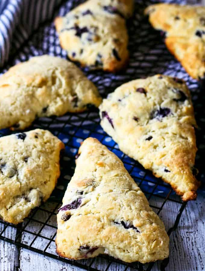 baking rack with multiple blueberry chocolate chip scones.