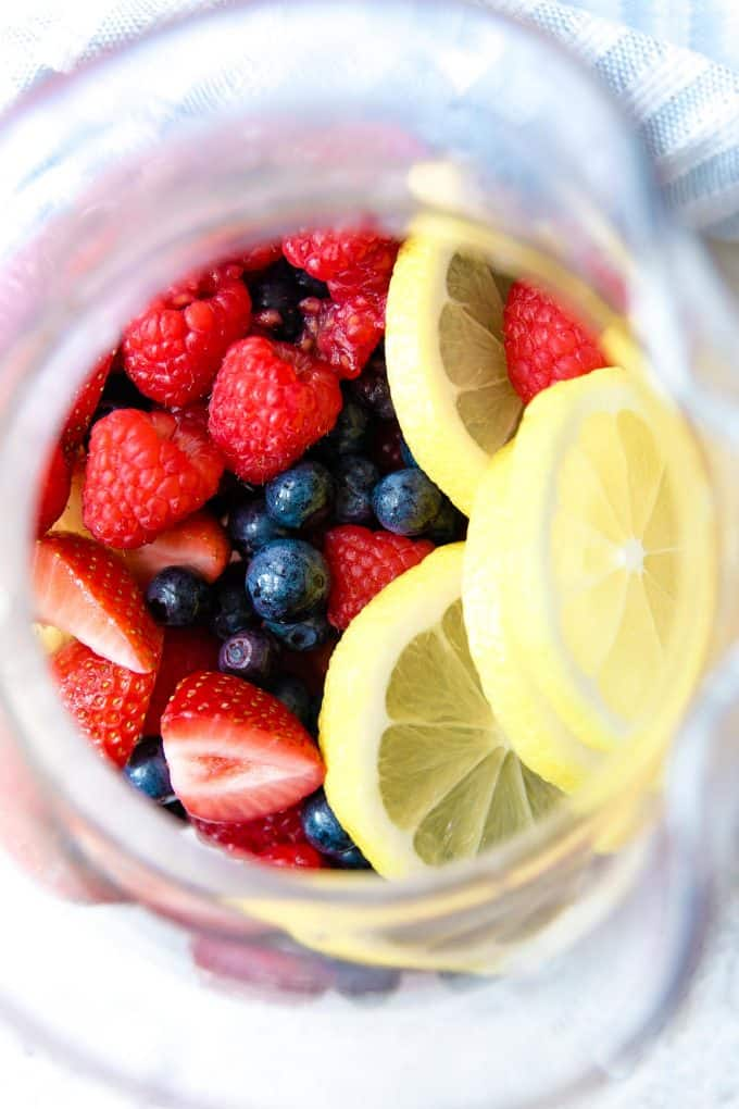 berries and lemon slices in a pitcher