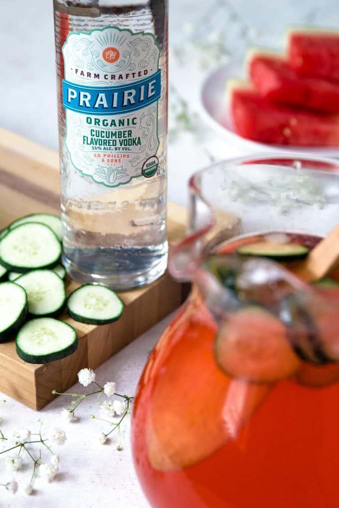 bottle of Prairie Organic Spirits cucumber vodka with a pitcher of cucumber watermelon punch