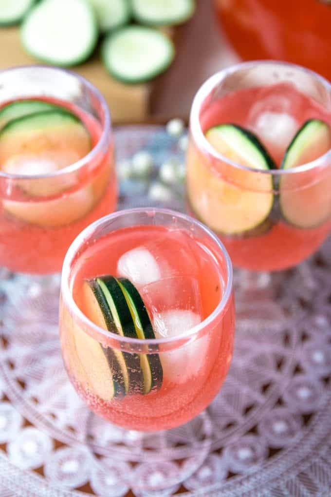 three glasses of cucumber watermelon punch on a patterned cutting board