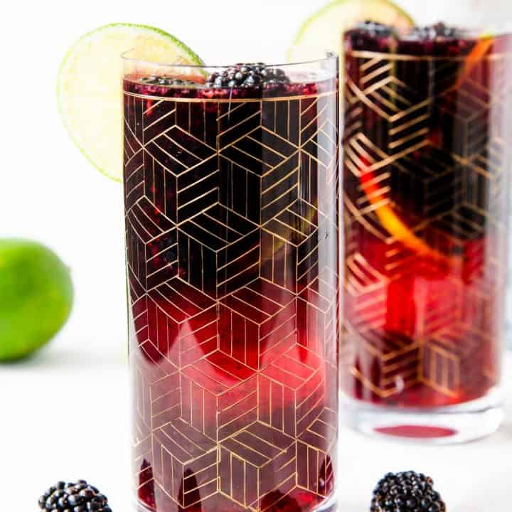 two gold etched glasses of blackberry sangria