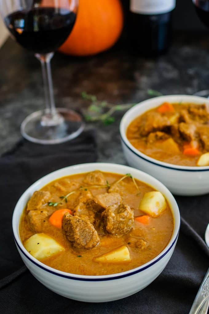 white bowl of pumpkin beef stew and a glass of red wine