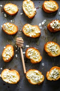 several blue cheese honey crostini on a sheet pan with a a honey stick