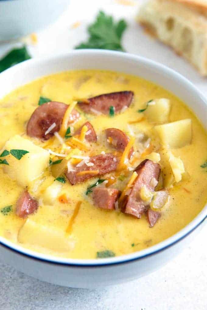 potato kielbasa soup in a white bowl with a blue rim