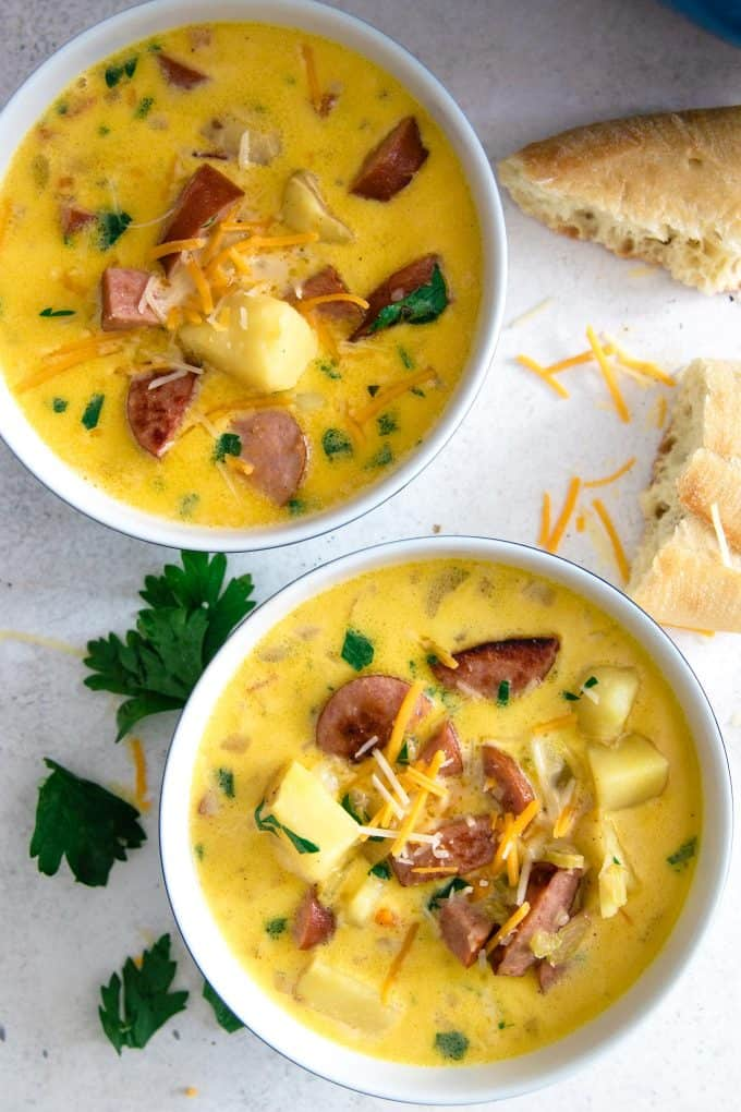 2 bowls of potato kielbasa soup with chunks of crusty bread