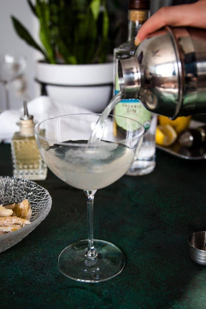straining a gin ginger martini into a martini glass