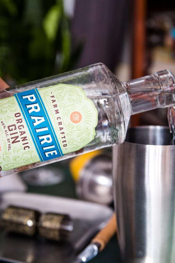 pouring Prairie Organic Spirits gin into a cocktail shaker