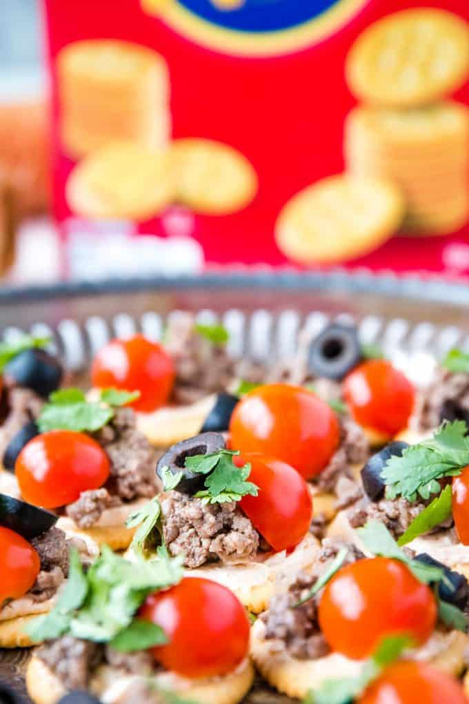 RITZ cracker topped with seasoned cream cheese and beef, tomato, cilantro, black olive