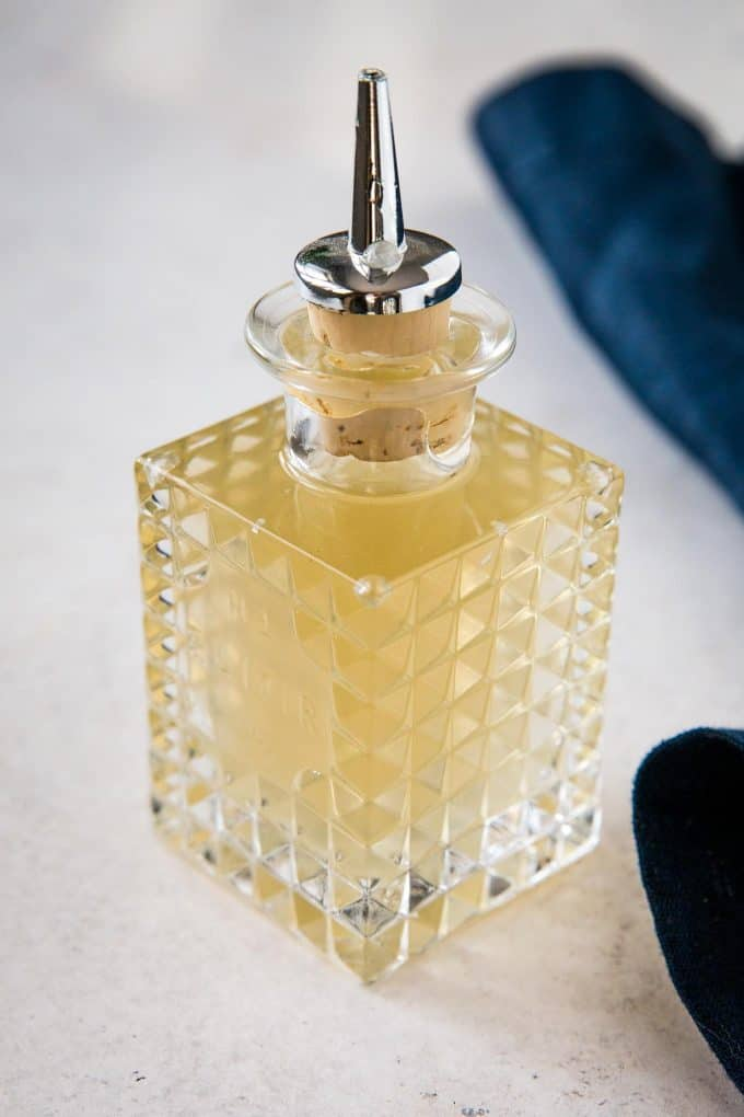 etched glass jar filled with ginger simple syrup