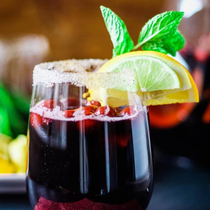 glass of Christmas sangria garnished with fresh mint and citrus and a rimmed glass