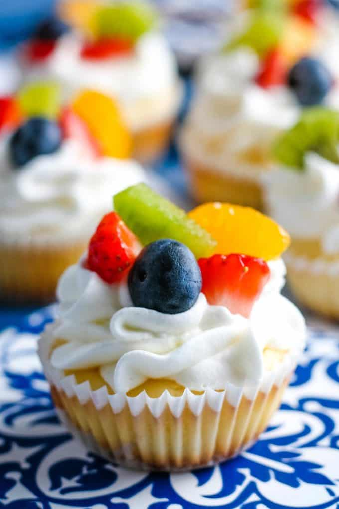 one mini cheesecake topped with fresh fruit and whipped cream