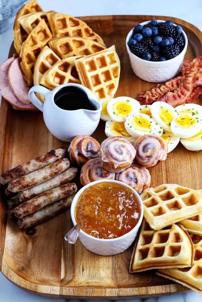 mini cinnamon rolls, deviled eggs, breakfast sausage, waffles, sausage links, Canadian bacon, and berries on a wooden board