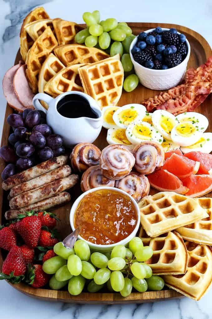 mini cinnamon rolls, deviled eggs, breakfast sausage, waffles, fruit, sausage links, Canadian bacon, and berries on a wooden board