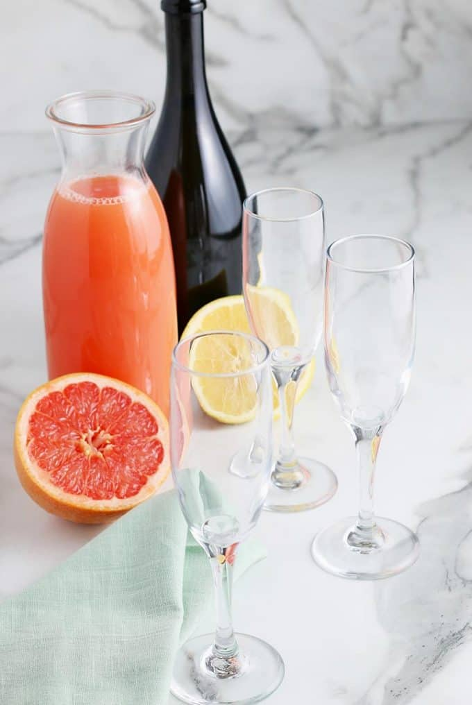 3 empty champagne flutes, one bottle of Prosecco and a carafe of grapefruit juice