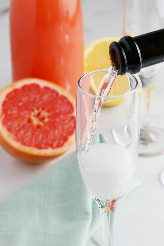 pouring champagne into a glass with a half grapefruit in the background