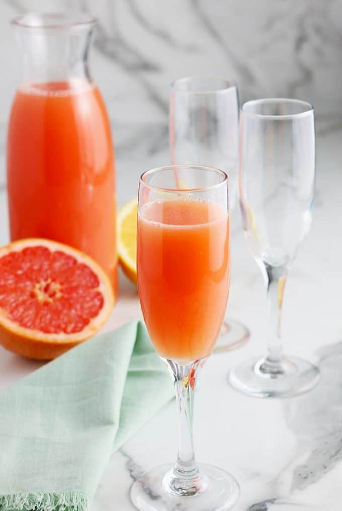 carafe of grapefruit juice, two empty champagne flutes and one grapefruit mimosa