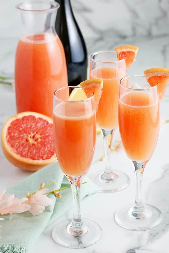 3 grapefruit mimosas in champagne flutes on a marble table