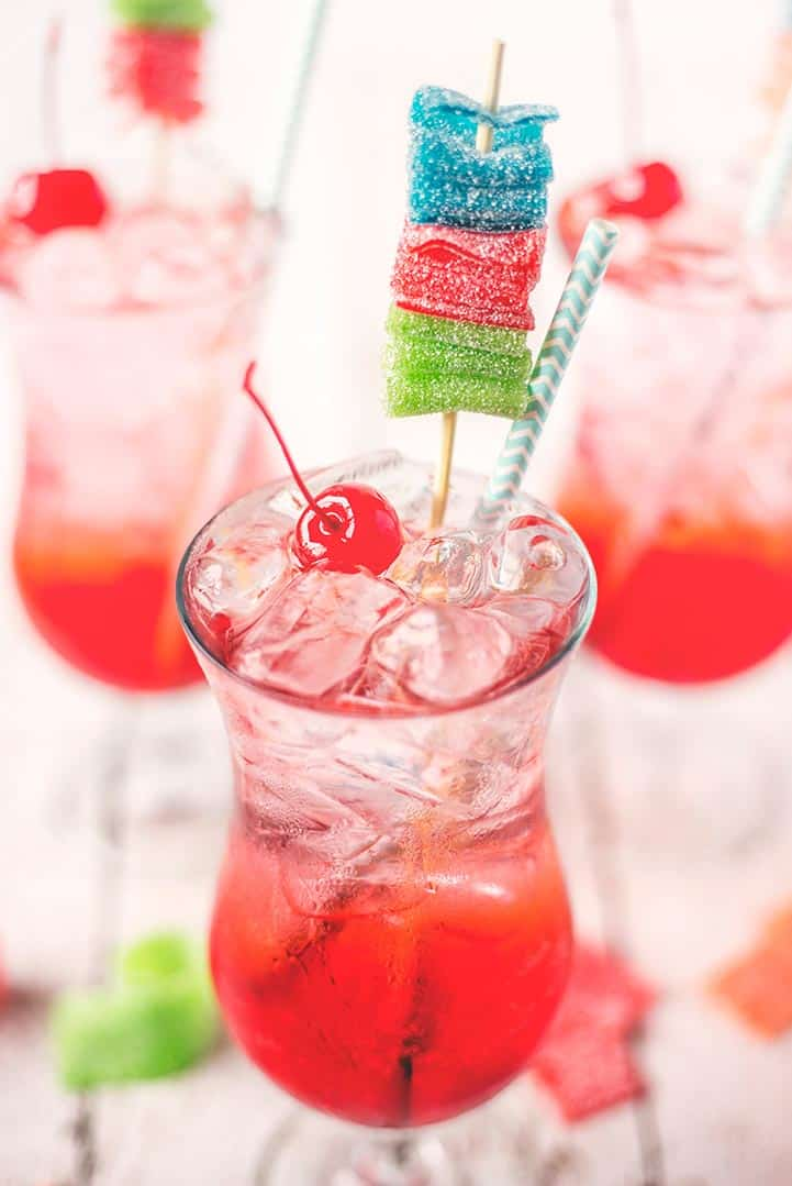 shirley temple garnished with a maraschino cherry, blue straw, and multicolored candy skewer