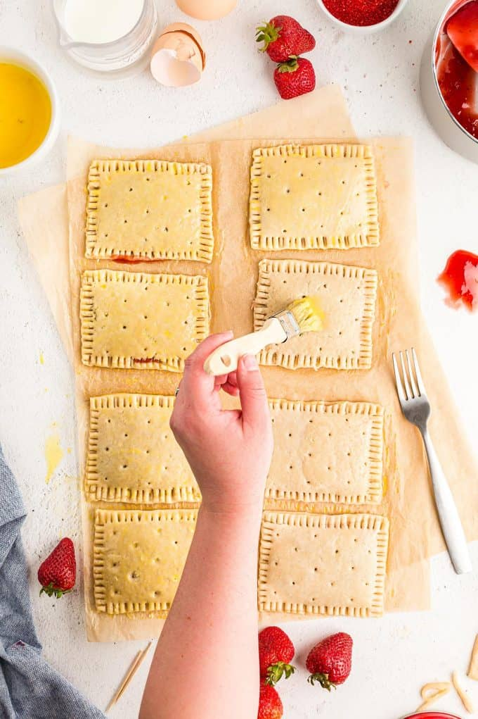 brushing egg wash on top of all of the unbaked homemade pop tarts